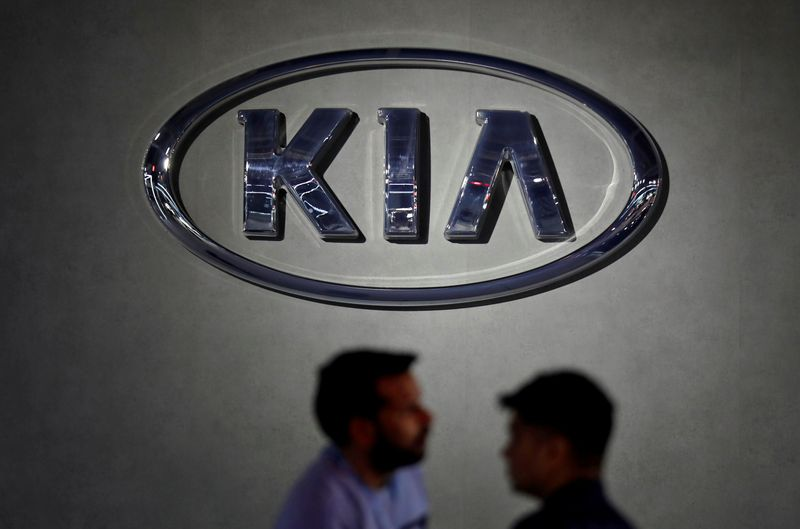 FILE PHOTO: Visitors walk past the logo of Kia Motors at its pavilion at the India Auto Expo 2020 in Greater Noida