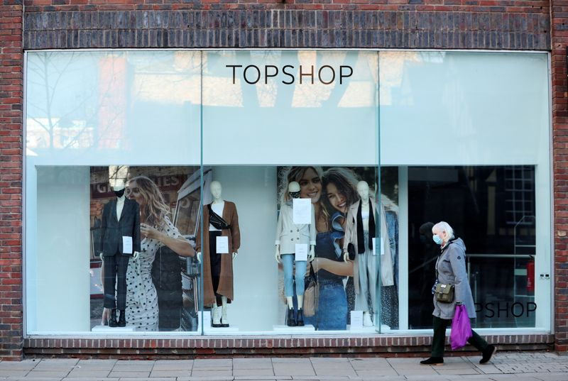FILE PHOTO: A woman walks past a TopShop, as the spread of the coronavirus disease (COVID-19) continues, in York