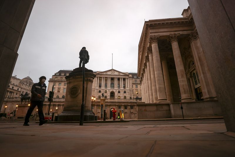 FILE PHOTO: A pedestrian walks past the Bank of England, in London