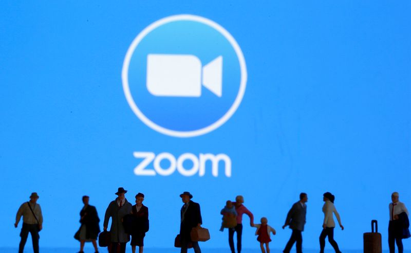 Small toy figures are seen in front of diplayed Zoom logo