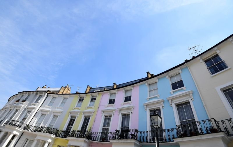 Houses are seen painted in various colours in a residential street in London