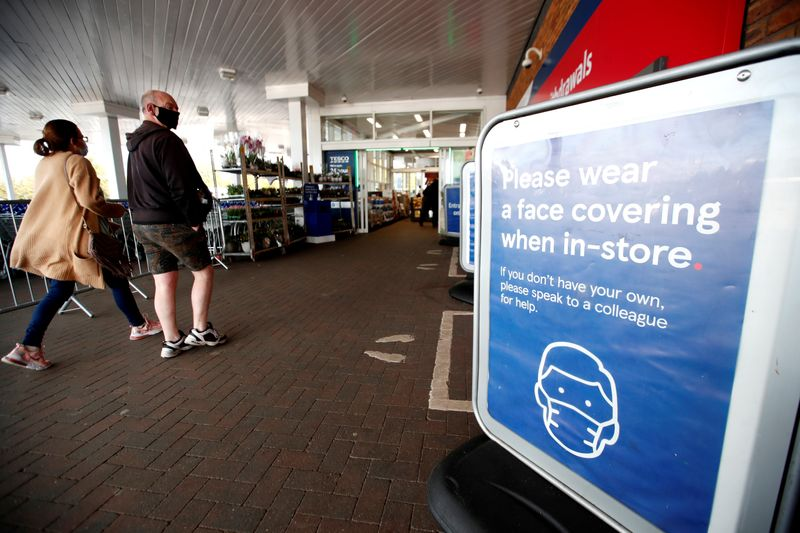 FILE PHOTO: An information sign requesting to wear masks is seen at the entrance to a Tesco supermarket in Hatfield