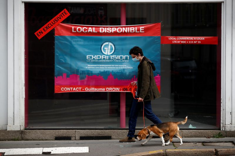 FILE PHOTO:  A man walks his dog past a commercial space for rent in a street in Nantes