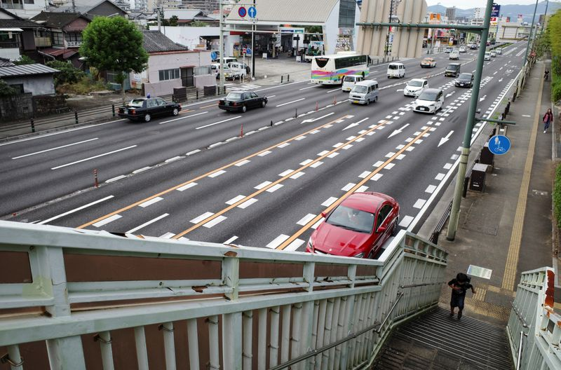 A schoolboy walks up the overhead bridge along a traffic junction in Beppu
