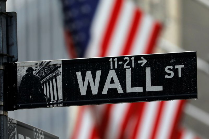 FILE PHOTO: Raindrops hang on a sign for Wall Street outside the New York Stock Exchange in New York
