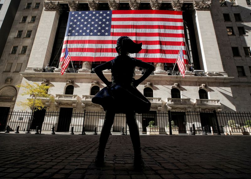 FILE PHOTO: The Fearless Girl statue is seen as the  U.S. flag covers the front facade of the NYSE in New York