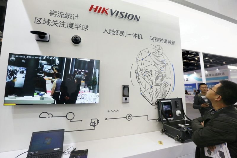 FILE PHOTO: Visitors are seen at a booth of security camera supplier Hikvision Digital Technology during an expo at the National Convention Center in Beijing