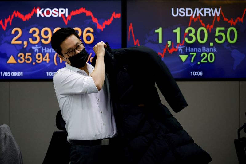 FILE PHOTO: A currency dealer walks past electronic boards showing the Korea Composite Stock Price Index (KOSPI) and the exchange rate between the U.S. dollar and South Korean won at a dealing room of a bank, in Seoul