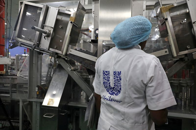 FILE PHOTO: A woman stands behind a machine that is part of a toothpaste manufacturing line at the Unilever factory in Lagos