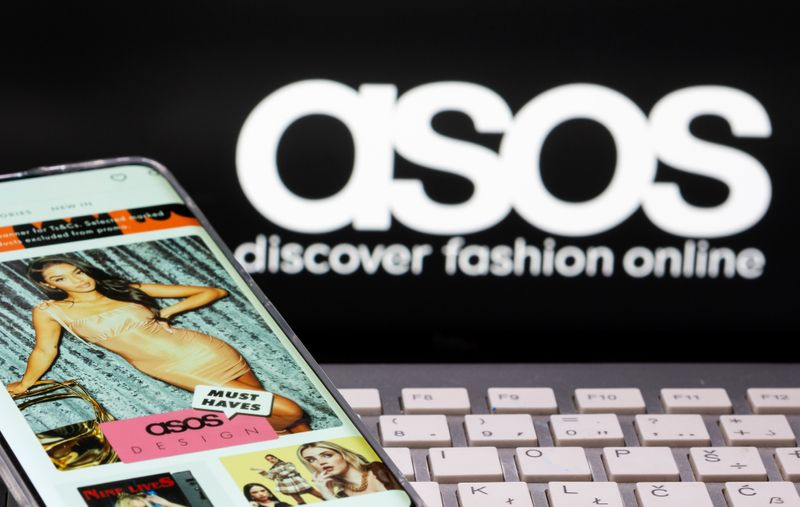 Smartphone with an ASOS app and a keyboard are seen in front of a displayed ASOS logo in this illustration picture