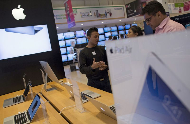 FILE PHOTO: An Apple salesperson speaks to customers at an electronics store in Mumbai