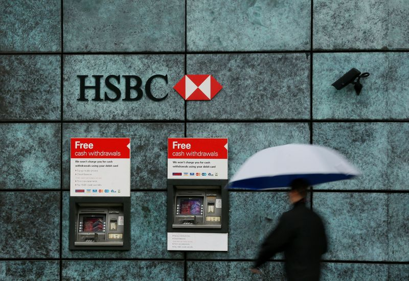 FILE PHOTO: A man walks past an HSBC bank branch in the City of London