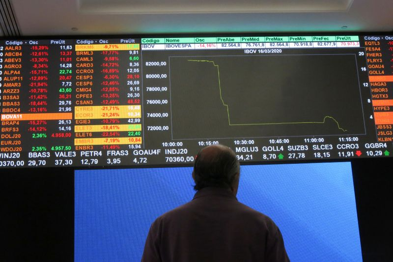 A man stands in front of an electronic display at B3 Brazilian Stock Exchange after an automatic circuit breaker was triggered this morning, in Sao Paulo