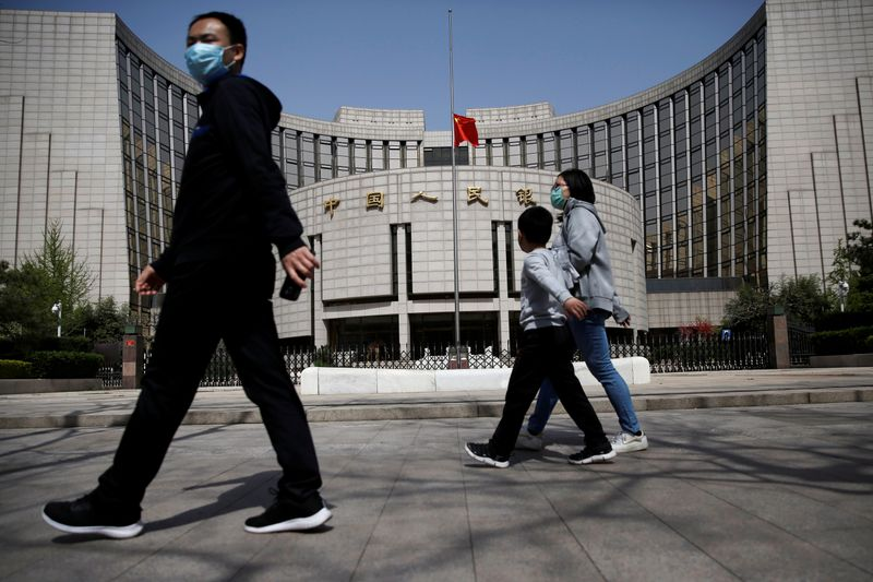 People wearing face masks walk past the headquarters of PBOC, where the Chinese national flag flies at half mast