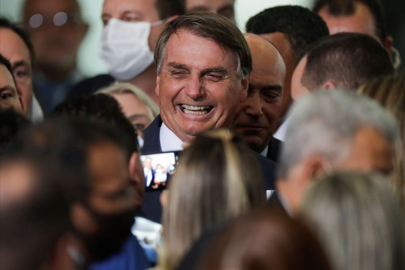 Brazil's President Jair Bolsonaro smiles near mayors after a ceremony to launch a program to help new mayors, at Planalto Palace in Brasilia