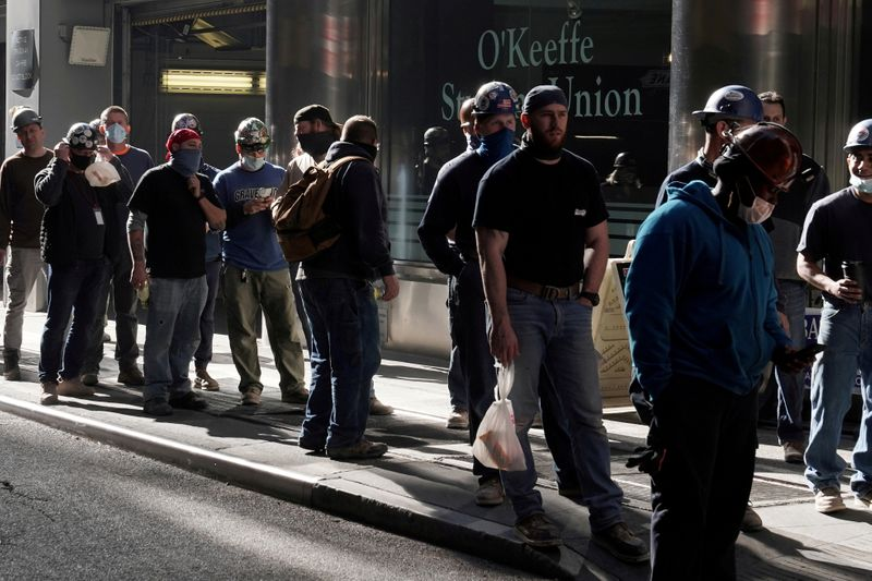 FILE PHOTO: Construction workers wait in line to do a temperature test to return to the job site