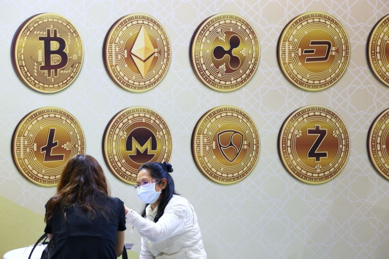 Customers talk against a backboard with signs of cryptocurrency during 2020 Taipei International Finance Expo in Taipei,