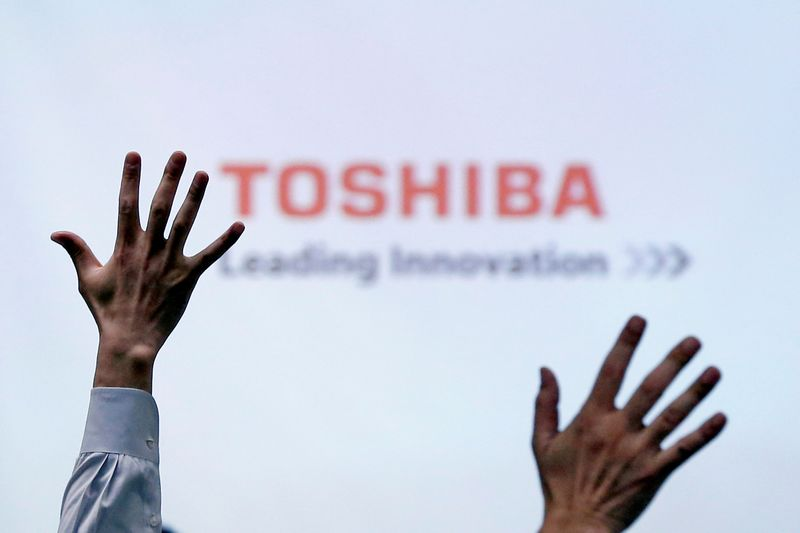 FILE PHOTO: Reporters raise their hands for a question during a Toshiba news conference in Tokyo