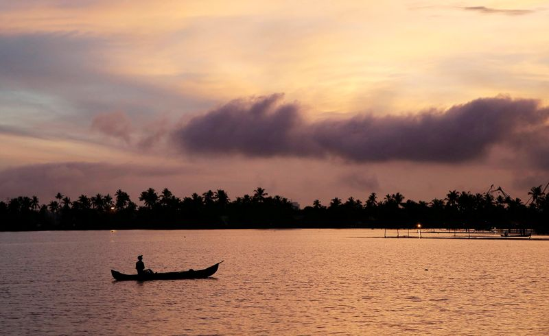FILE PHOTO: A man rows his boat in the tributary waters of Vembanad Lake against the backdrop of pre-monsoon clouds on the outskirts of Kochi