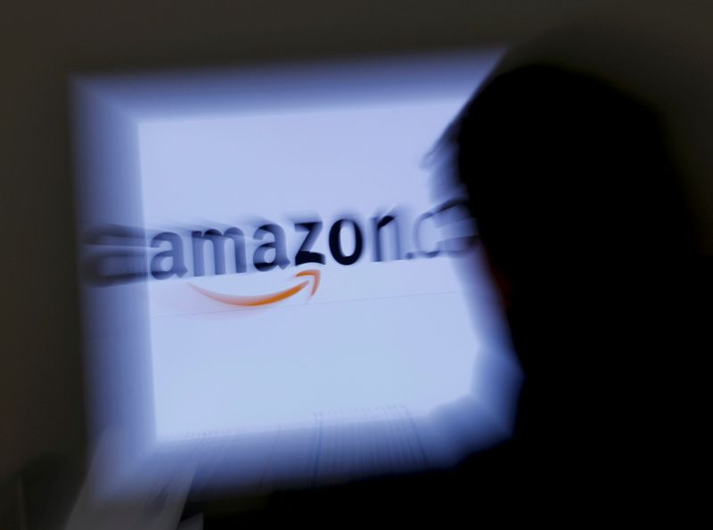 FILE PHOTO: A zoomed illustration image of a man looking at a computer monitor showing the logo of Amazon is seen in Vienna