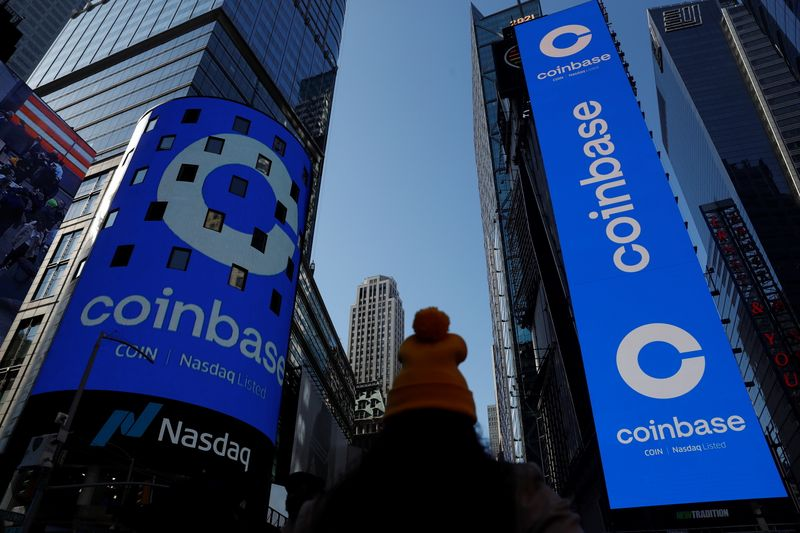 The logo for Coinbase Global Inc is displayed on the Nasdaq MarketSite jumbotron and others at Times Square in New York