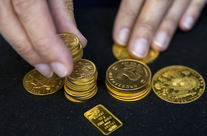 FILE PHOTO: A worker places gold bullion on display at Hatton Garden Metals precious metal dealers in London