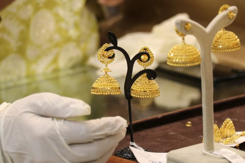Customer looks at gold earrings at a jewellery showroom during Dhanteras in Mumbai
