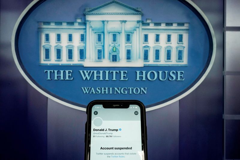 FILE PHOTO: A photo illustration shows the suspended Twitter account of former U.S. President Donald Trump on a smartphone at the White House briefing room in Washington